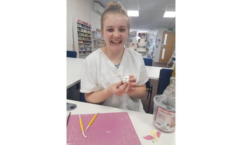Young girl smiling during making her manikin at one of our Junior workshops.